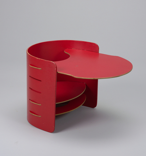 Child's semi-circular chair in red-painted plywood; pierced with slats allowing for adjustable flat seat and additional parts to be removed and reinserted at various hights; curved table top inserted in chair.