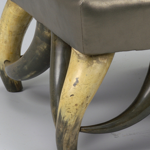 Bow-shaped horn supported square ottoman upholstered in gold leatherette. Part of group with armchair 1986-39-1.