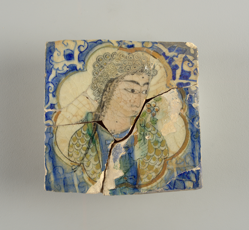 Square tile, centered with bust of woman in cusped medallion. Subject, head one quarter to right, holds flower to nose, wears gown with imbricated patter. Colors: flesh, green, blue, and olive brown.