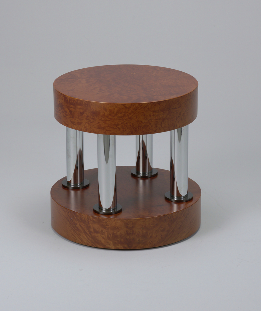 Thick, circular briarwood seat and base with four thick vertical tubular chromed metal supports mounted in between.