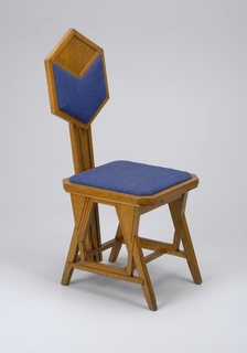 Side chair with octagonal seat, hexagonal back supported by three central vertical members which rise from seat stretcher. Legs attached at slanting anglesto form triangular voids and solids and irregular hexagonal voids at intersections with stretchers. Slip seat and back panel covered in blue fabric.