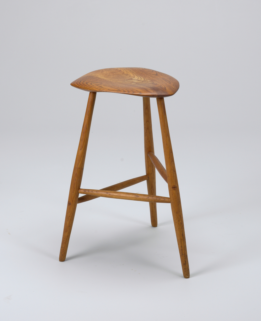 Carved, contoured D-shaped seat on three tall tapering legs, circular in section; legs with three stretchers, each set at a different height.