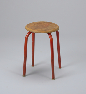 Circular, concave oak seat mounted on four tubular metal legs enamelled red.