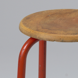 Circular, concave oak seat mounted on four tubular metal legs enamelled red.