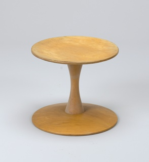 Circular seat on shaft, tapered at center, surmounting slightly domed circular base.