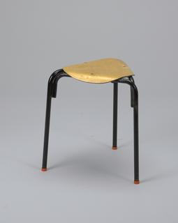 Triangular seat fromed of circular plywood panel with downward-molded edges; seat mounted on black-painted tubular metal three-legged base; red caps on feet.