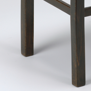 Ebonized wood form composed of rectangular seat up-curved at ends mounted on curving four-leged base with horizontal black stretchers between legs.