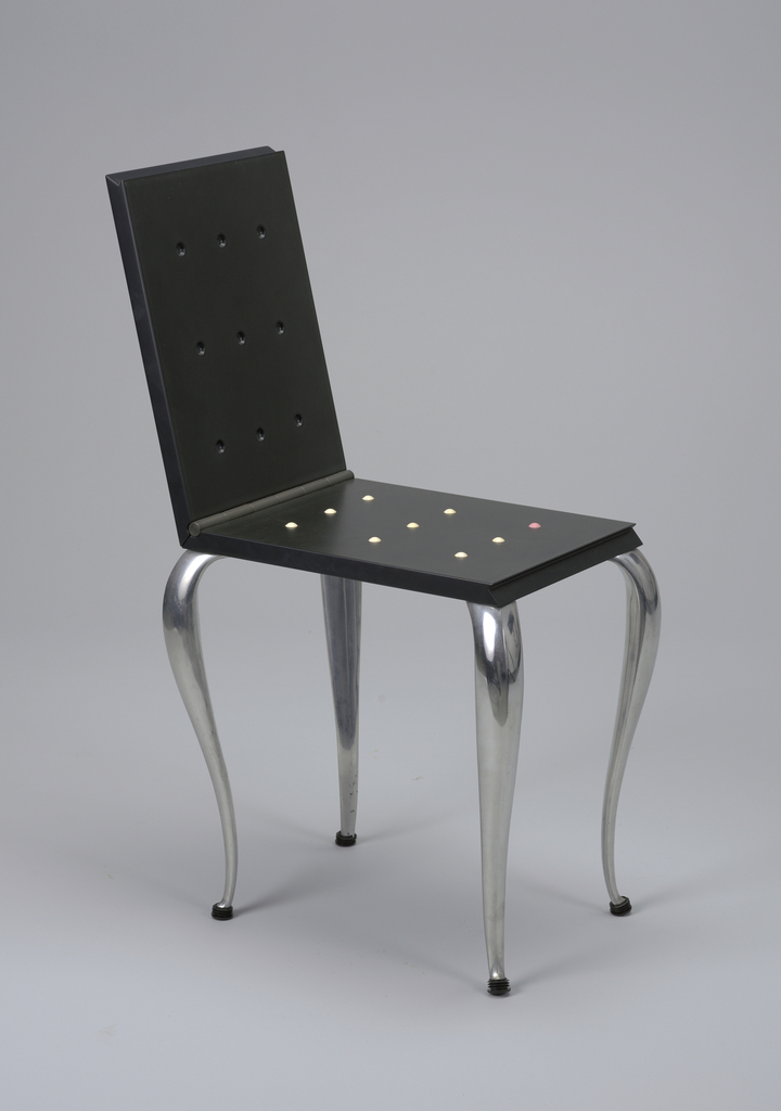 Black, rectangular seat on tapering aluminum cabriole legs; seat, hinged on short side, flips open to form chair having three rows of pink rubber studs on seat and corresponding indentations in back.