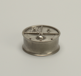 Cylindrical inkstand divided into three parts consisting of removeable wedge-shaped sand caster with pierced top; wedge-shaped compartment with fitted, knoped lid; semi-circular inkwell with hinged dome cover; rim with semi-circular flange having three holes.