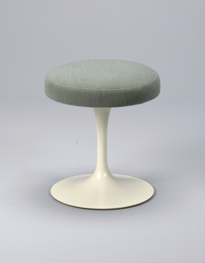 Circular seat covered in green wool upholstery on white stem-like base spreading to broad circular foot.