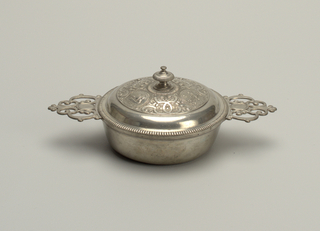 Bowl with ornamental scroll handles. Cover has three medallions inscribed.