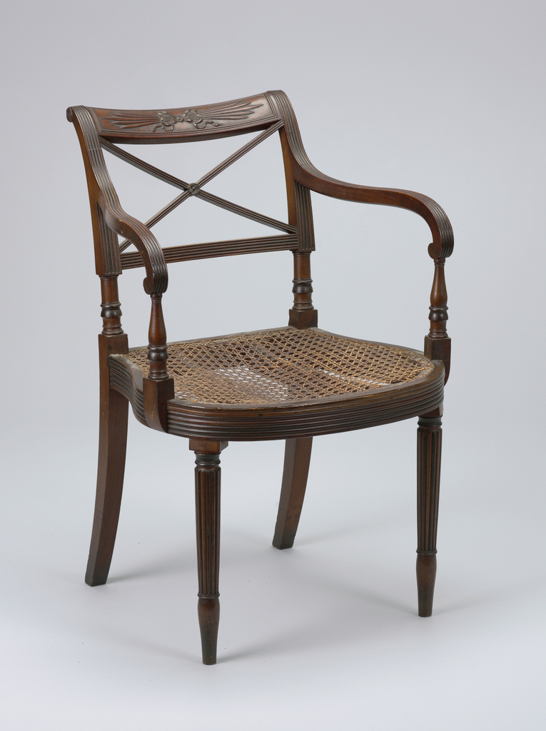 """Rounded reede seat rail; rounded and reeded tapering legs.  Top rail carved with """"thunderbolt design"""" representing streaks of lightning, tied with bow.  Below top rail, two diagonal, crossing bars, reeded.  Arm reeded on top surface; supported on urn-shaped baluster."""