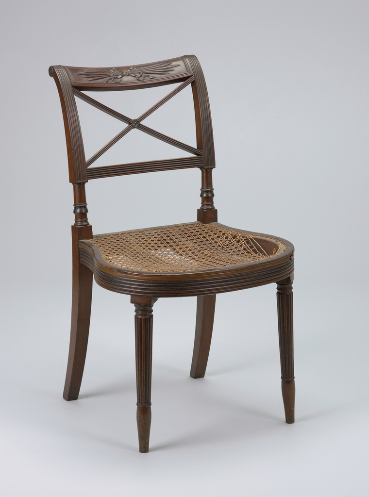 """Mahogany; caned seat covered with upholstery.  Rounded and reeded seat rail; rounded and reeded tapering legs. Top rail carved with """"thunderbolt"""" design tied with bow. Below top rail, two diagonal, crossing bars, reeded.  Set covered with green cotton velvet."""