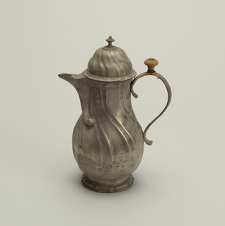 On shaped, flaring foot of a gadrooned pyriform body with attached spout twisted into scroll and knob. Domed, hinged cover. Strap handle, wound with cane, and wooden knob.