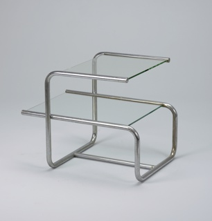 Two-tiered rectilinear form, the chromed, bent tubular metal frame with rectangular clear glass top surmounted by square clear glass shelf.