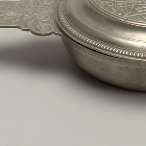 Circular bowl with baroque cartouche-shaped handles moulded with decoratve scrolls, the circular lid also decorated with spiral lambrequins and scrolls.