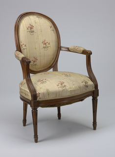 Upholstered armchair, exposed wooden frame.  Oval back, serpentine-fronted seat, open arms with upholstered arm rests, tapered legs, each with five deep flutes with wooden insert in lower half of each flute.  Upholstered with striped flowered silk with pinkish-beige background.
