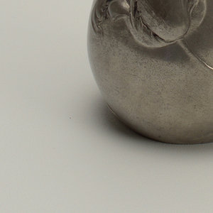 A pewter pitcher in an abstract form.