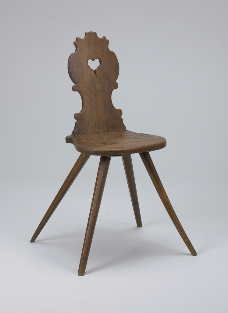 This chair consists of two pieces of hard wood (seat and back) jointed at the back of the seat.  The back tapers slightly and is characterized by leaf-like carvings.  A small heart is cut out of the upper, central area of the seat back.  The chair's seat is a simple slab of wood.  The chair has four legs, each flaring outwards and tapering as they meet the floor.