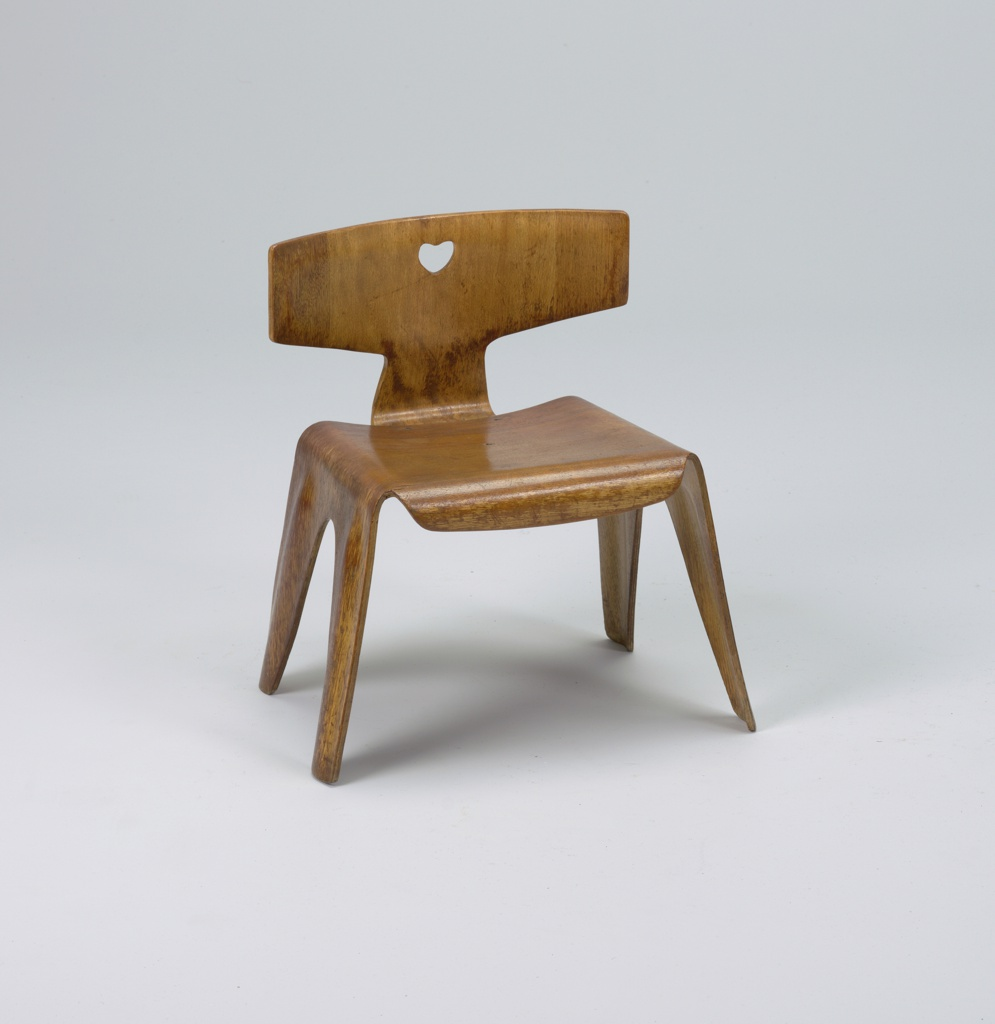 Molded, laminated plywood form of T-shaped back, square seat, the sides bending to form  four flat legs; front of seat bent down to form short apron; back with small heart-shaped cut-out in center, attached to seat with three metal fasteners.  Natural finish.