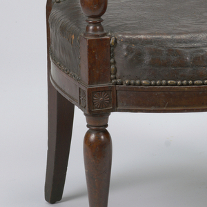 Rectangular back.  Flat padded arms curve outward and are supported by their turned stumps which are in one with the front legs, similarly turned.  Bowed front and side seat rails received by rosetted reserves.  Rear legs square and tapered.  Upholstery is black leather nailed to frame.