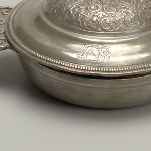Ecuelle (a): shallow bowl with reinforced rim and horizontal handles with scroll relief and slit. Lid (b): domed cover, upper part with conventionalized symmetrical relief decoration; edge reeded; flattened ring handle. Engraved shield with three cross on bend.
