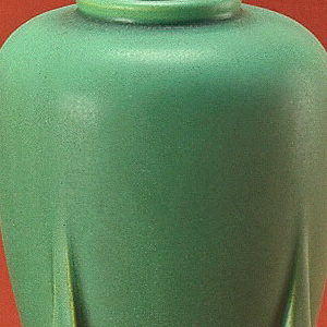 Moss green, four-handled buttress form. Buff-colored clay body, cast. Baluster body tapering to a point at base; low ring neck on shoulder. Supported by four buttress-like feet that extend upward to mid-body. Allover pale silvery-green matte glaze; no decoration. Glaze thick in recessed areas, some crystalization. Bottom and interior glazed.