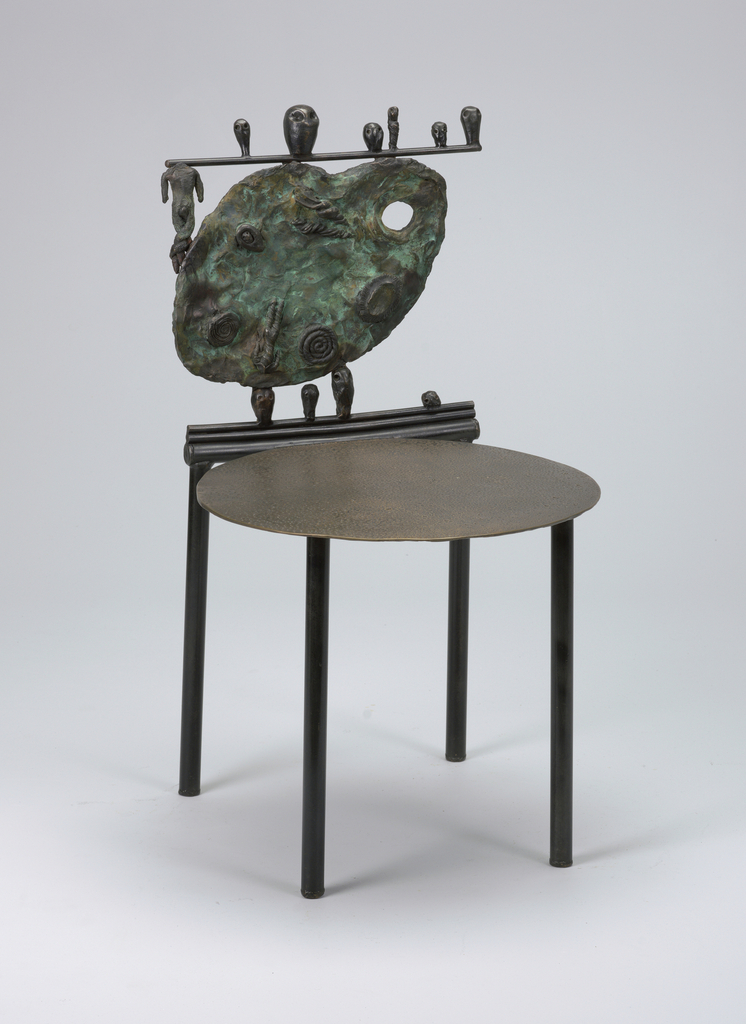 "Flat disk seat on four straight cylindrical legs; back composed of cast bronze painter's palette decorated with spirals; ""crest rail"" consisting of a horizontal rod, a headless figure below the rod, to left of palette, and six different sized heads sitting on the rod; three cast bronze heads situated between the seat and back, supporting the back, with a fourth head to the right."