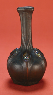 Bronze-plated vase with six inlaid scarabs.  White clay body, semi-porcelain, cast. Bulbous body with long slender neck with slightly flaring rim. Raised ribs on neck and extending down body, incorporating six iridescent amber glass scarabs into the recessed areas around the shoulder. Allover electro-plating of bronze, with dark patina.