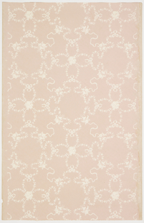 Meallion-like shapes created with floral swags, connect by ribbons and bow knots. Printed in white on a pale pink or mauve ground.