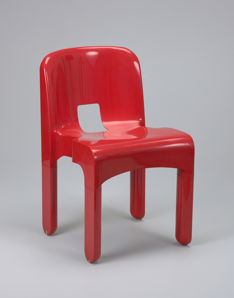 Red plastic one-piece stackable side chair with curved back and flat seat; rectangular opening where back curves into seat; four flat, rectilinear legs and shaped seat edge for ease of stacking.