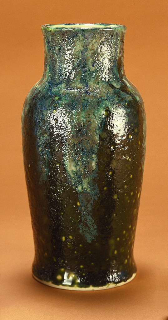 """Gray-white stoneware body, thrown. Baluster body with cylindrical neck, slightly flaring; base also slightly flaring; not foot. Exterior covered with an olive green volcanic glaze pitted with yellow-green """"craters.""""  A blue-gray and green glaze flowing over the base glaze extending from rim to shoulder, also pitted. Bottom not glazed. Interior covered with clear glaze."""