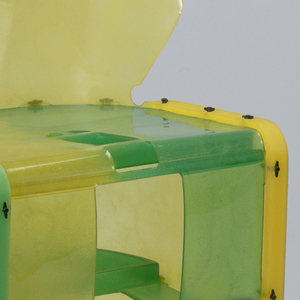 Chair formed of assembled sheets of poured resin in shades of yellows to greens; oval back with attenuated vertical V-shaped split in center, attached to U-shaped seat on base formed of curving sheets.