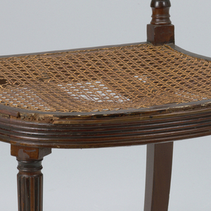 """Rounded and reeded seat rail; rounded and reeded tapering legs.  Top rail carved with """"thunderbolt design,"""" tied with bow.  Below top rail, two diagonal, crossing bars, reeded."""