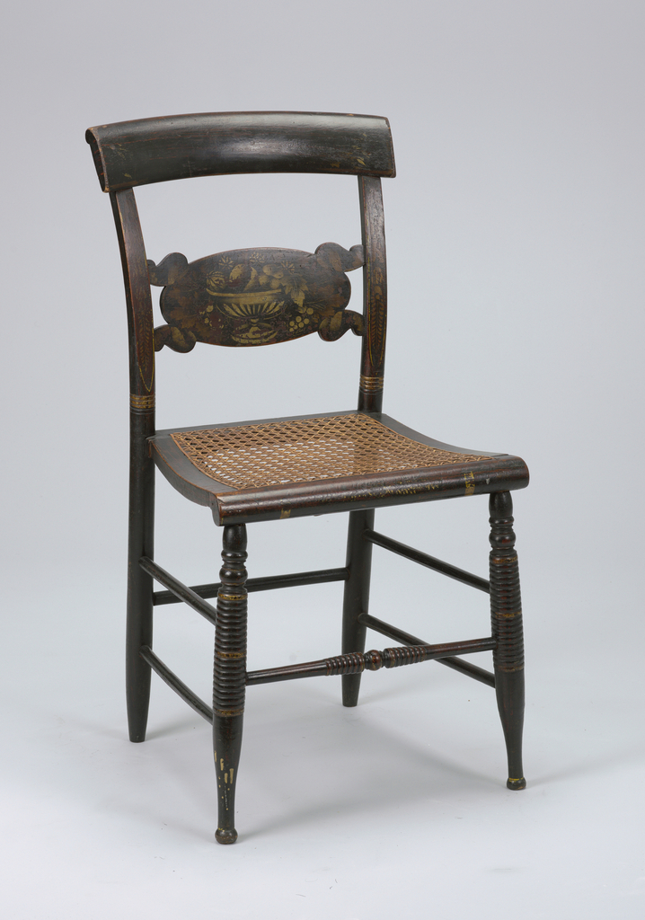 """Rolled pillow back and front seat rail; so-called """"turtle"""" slat stencilled with design of footed bowl of fruits.  Turned straight front legs on button feet.  Four lateral and two longitudinal turned stretchers.  Caned seat.  Gilt bandings on black ground."""