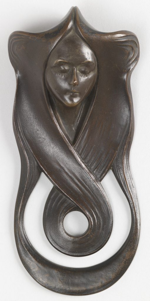 modeled as a woman's head with her long, flowing hair surrounding the opening for the doorbell, and terminating in overlapping scrolls