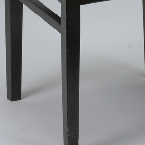 A side chair with a square back made up of 8 squares and one solid wood square in the center. Straight legs and no arm rests, with a wood seat.