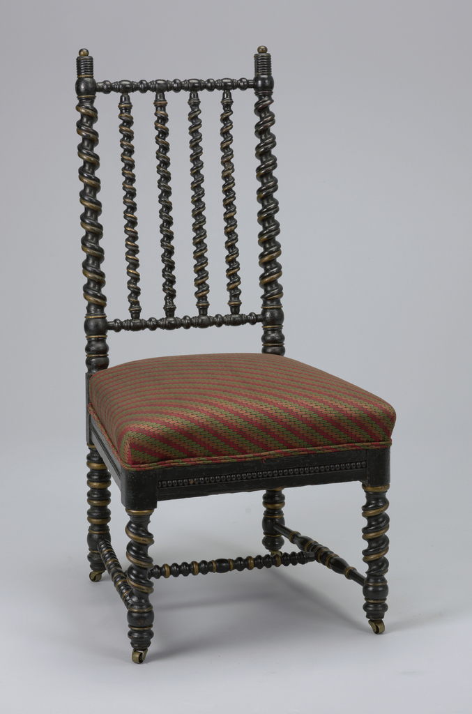 Twirled turned stiles, rails and legs. Metal casters on feet.  Seat upholstered in green, red, pink fabric.