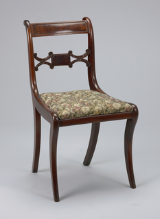 Back legs flat-sided, front legs flat excepting rounded front face; legs curve outward toward bottom, and back legs incline toward each other at bottom.  The chair's back corner posts terminate in a volute-like form at the top of the chair.   The chair's top rail, slightly arched, is bowed towards the back.  A rectangular panel of inset veneer is surrounded by beading.  The chair's splat is horizontal, composed of a small oblong-shaped rectangle faced with veneer, flanked on either side by horizontal coupled C-scrolls covered with foliage.  The C-scrolls terminate in volutes.  The seat flares from back to front, with straight edges.