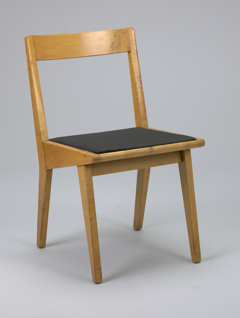 Wooden stacking chair, angular with slightly curved band for back and black textile for seat.