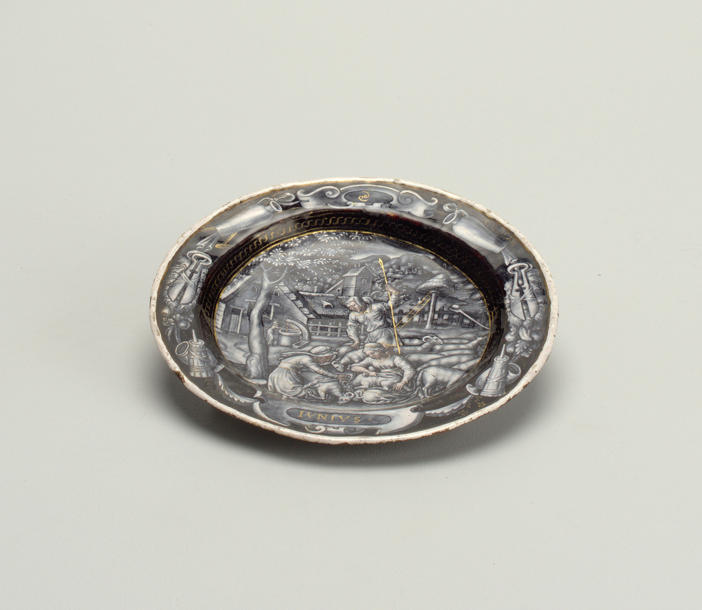 "Limoges enamel small plate decorated en grisaille, with flesh tones and heightened in gold, depicting peasants shearing sheep, captioned: ""IVNIVS"". On reverse, lobster at center encircled by scrollwork and a winged putto and lion."