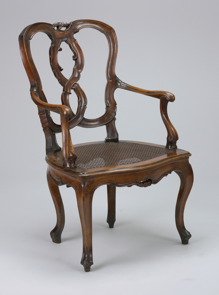 The open back and splat are formed by two intertwined curvate members moulded with scrolls.  Curved arms and arm stumps.  Cabriole front and rear legs. seat caned.