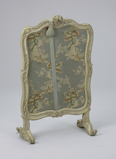 a) Vertical contoured frame, painted gray, enclosing (b) sliding silk-covered panel. Frame (a) has molded edges, two roses with leaves carved top center on both sides; foliage and scrolls on sides; flowers, foliage and scrolls at center bottom and on sides of scrolled cross feet. Sliding panel (b) covered with floral-and-ruin patterned silk on blue ground, has contoured top and weighted pull on blue silk cord. Panel enters frame through slot at top of frame.