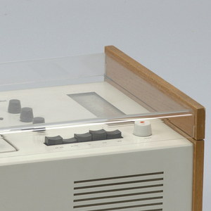 Rectangular form; white metal housing flanked by ash wood sides; turntable and arm on left, control knobs and radio tuner on the right. Hinged cover of clear plastic with ash wood strips on sides.