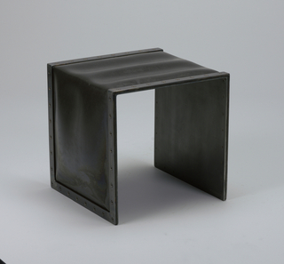 Three-sided square form of sheet steel in dark finish; black rubber sheet stretched over form and slightly inflated. Narrow steel band riveted along edges to hold rubber sheet in place.