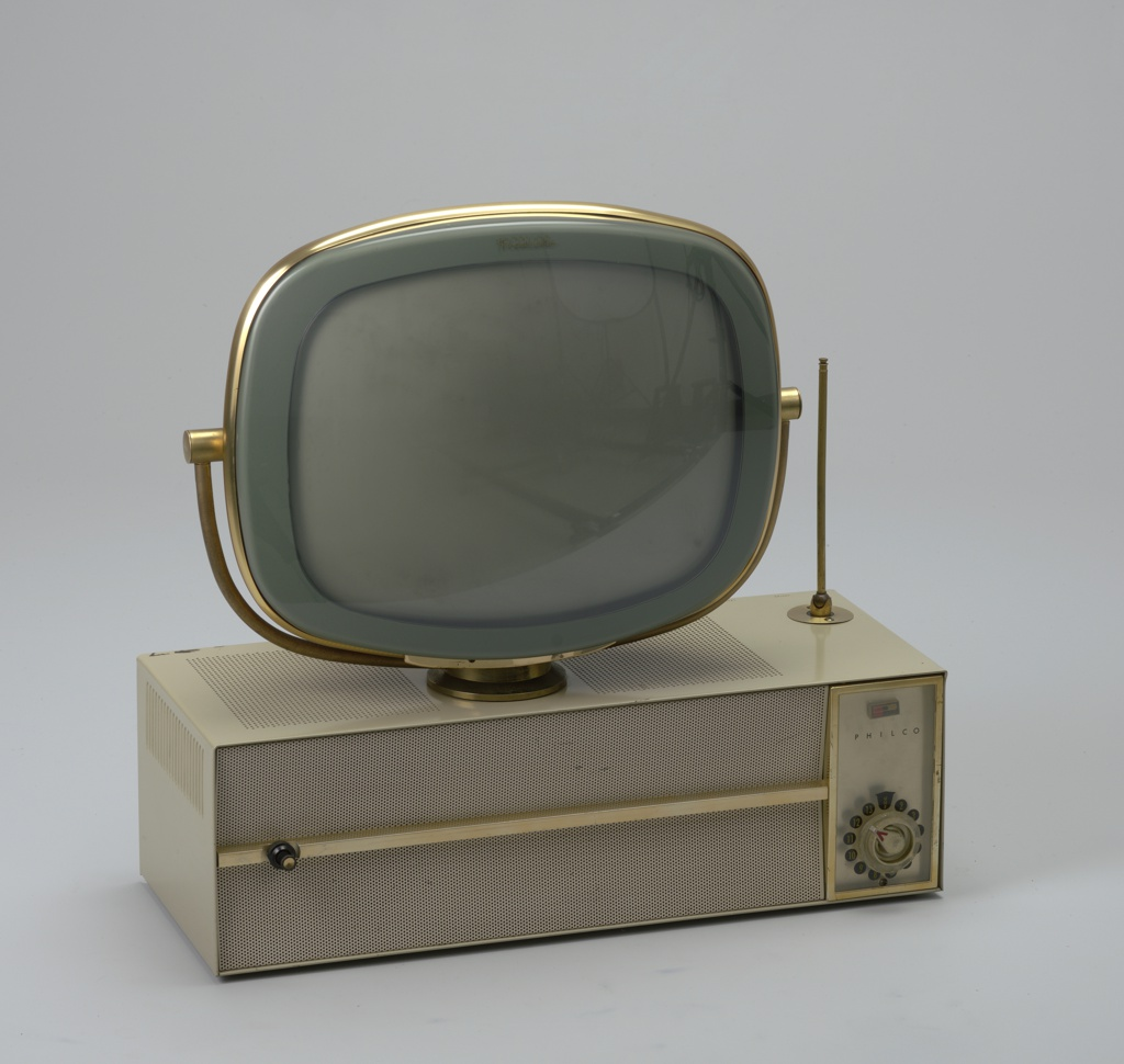 "Swiveling cathode ray television tube mounted on top of rectangular, white enameled metal case; top of case perforated; swiveling antenna mounted on rear right corner; front composed of perforated grill horizontally bisected by brass band and upright rectangular plastic panel on right with ""P"" logo and ""Philco"" above circular channel control knob."