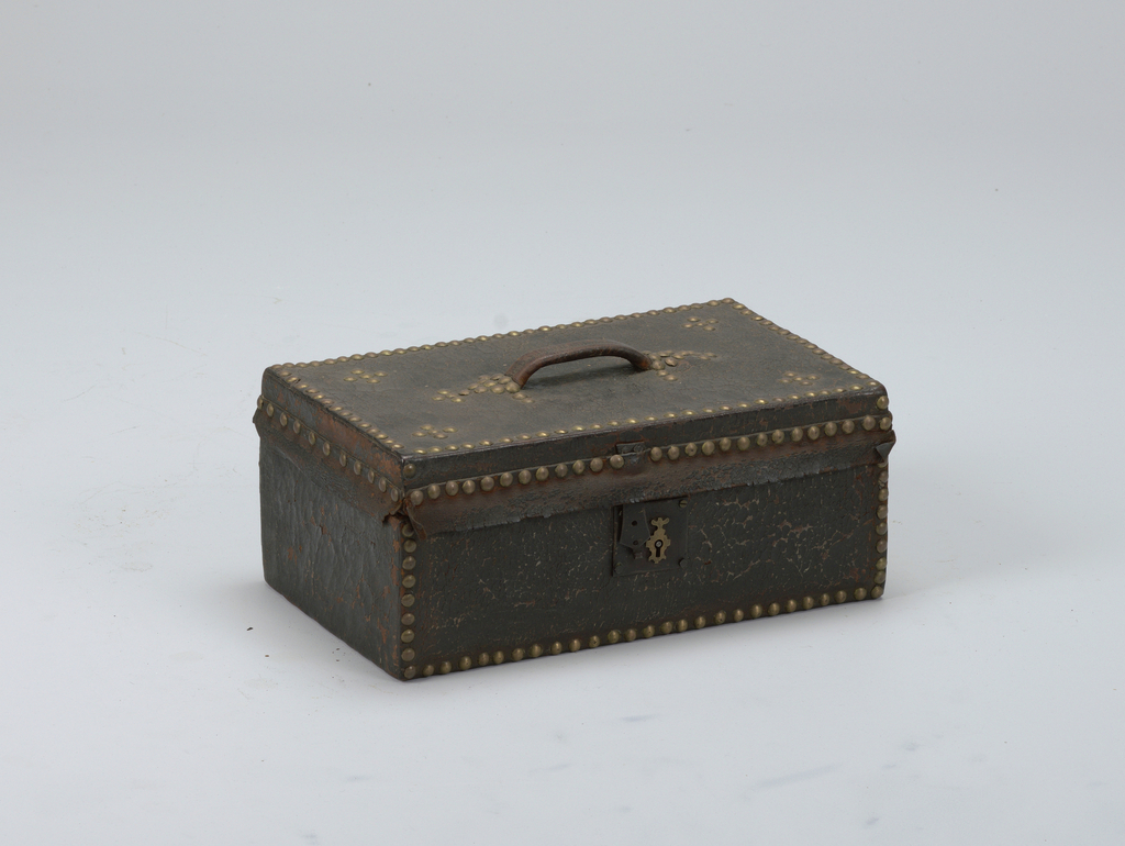 Rectangular box covered with black leather (now in crazed condition), with hinged lid, iron lock with patterned brass escutcheon, leather handle (center top), flaps of leather extending from front and side edges of top.  Leather attached by rows of round-headed brass tacks, patterns of tacks on top. Lined with printed fabric, small-patterened red, white, black ground. Leather hinge, interior.