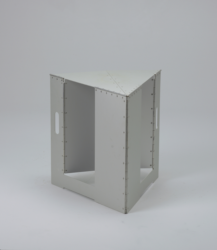 Triangluar form composed of flat, riveted aluminum panels; sections hinged to fold into flat portable trapezoidal form; two panels cut with broad slits to form handle when folded.