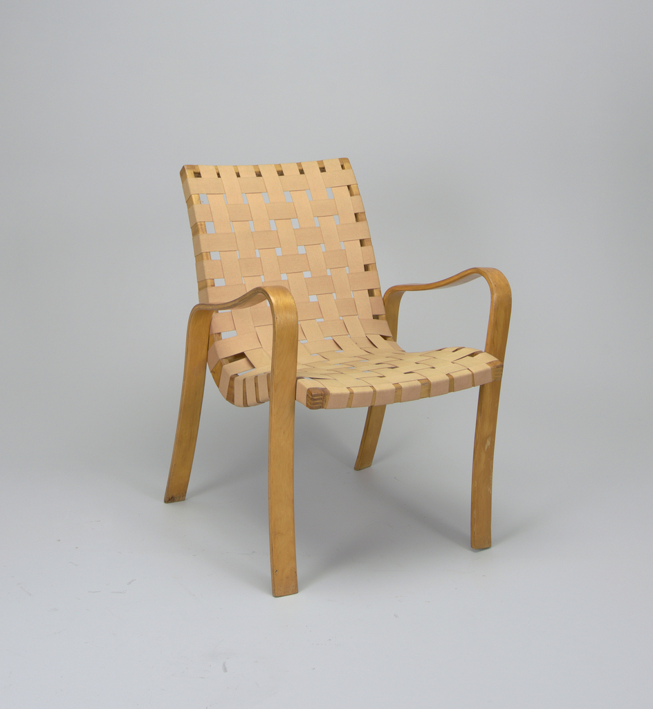 Fabric-webbed back and seat placed into bent wood frame.  Front and back legs continious with armrails; one piece of bent wood on each side of chair.  Seat frame also of bent wood, with rectilinear crest and seat rails.
