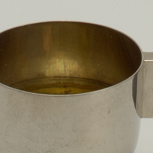 Semi-spherical bowl with metal cuff affixed to a rectangular wooden handle with exposed rivets. Stabilizing feet at bottom. Triangular spout. Slightly tarnished surface.